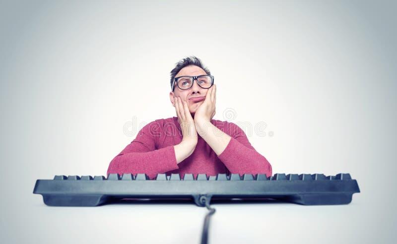 玻璃的想法的人在计算机前面的一个键盘后,在他的手上拿着他的头 E 库存照片