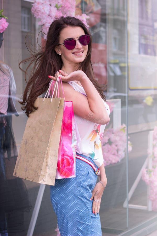 玻璃的时尚美丽的女孩与购物 库存图片