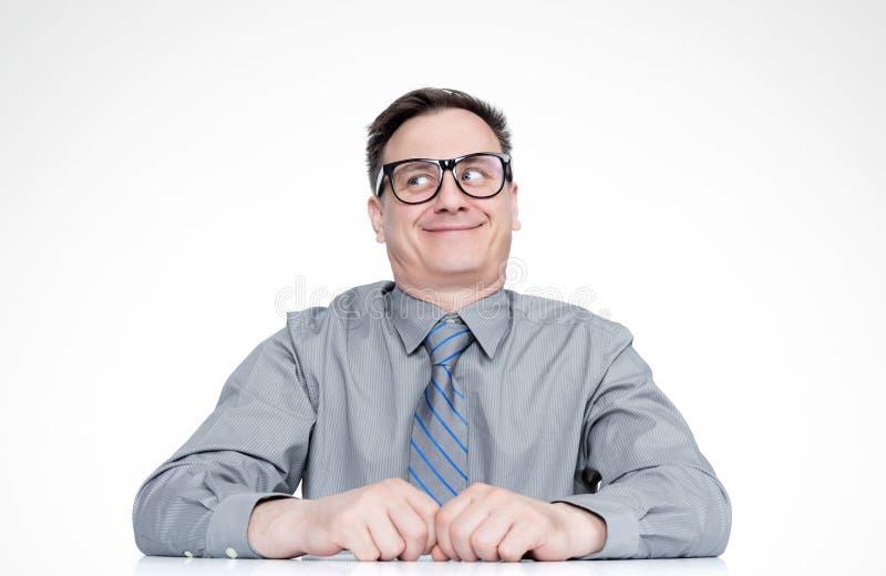 玻璃的狡猾棘手的情感微笑的人认为看在边的,在轻的背景 免版税库存照片