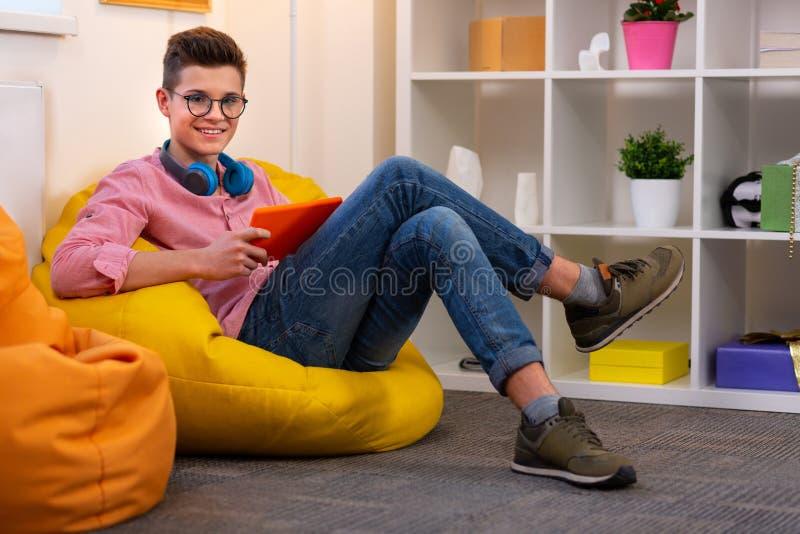 玻璃的现代学生坐装豆子小布袋椅子读书eBook 图库摄影