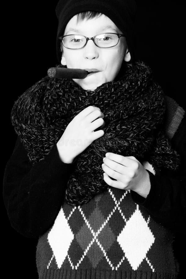玻璃的男孩书呆子与cigarsmall微笑的男孩或逗人喜爱的书呆子孩子在玻璃、帽子和时兴的被编织的围巾在黑色 免版税库存照片