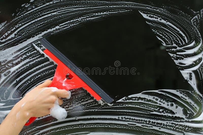 玻璃的红色橡皮刮板 库存照片