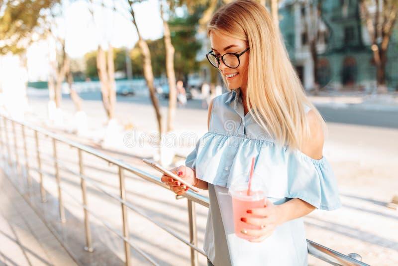 玻璃的美丽的女学生与举行的鸡尾酒在手中 免版税图库摄影