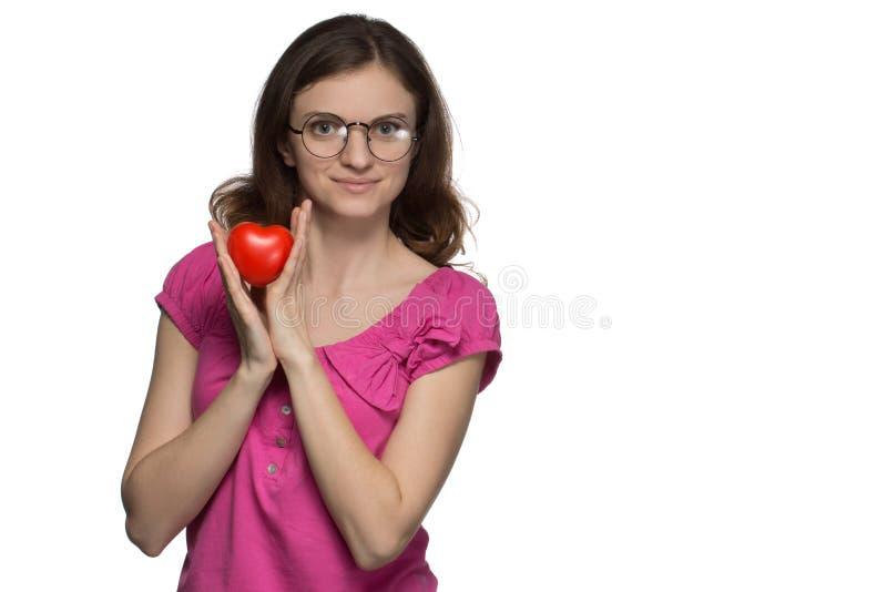 玻璃的美丽的深色的女孩微笑并且拿着在h的心脏 免版税库存照片