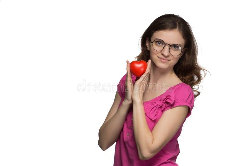 玻璃的美丽的深色的女孩微笑并且拿着在h的心脏 库存图片