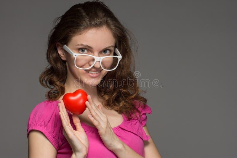 玻璃的美丽的深色的女孩微笑并且拿着在h的心脏 免版税库存图片