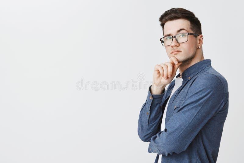 玻璃的聪明的人和在转动在照相机的外形的蓝色衬衣身分与周道的坚定和对表示怀疑的神色 图库摄影