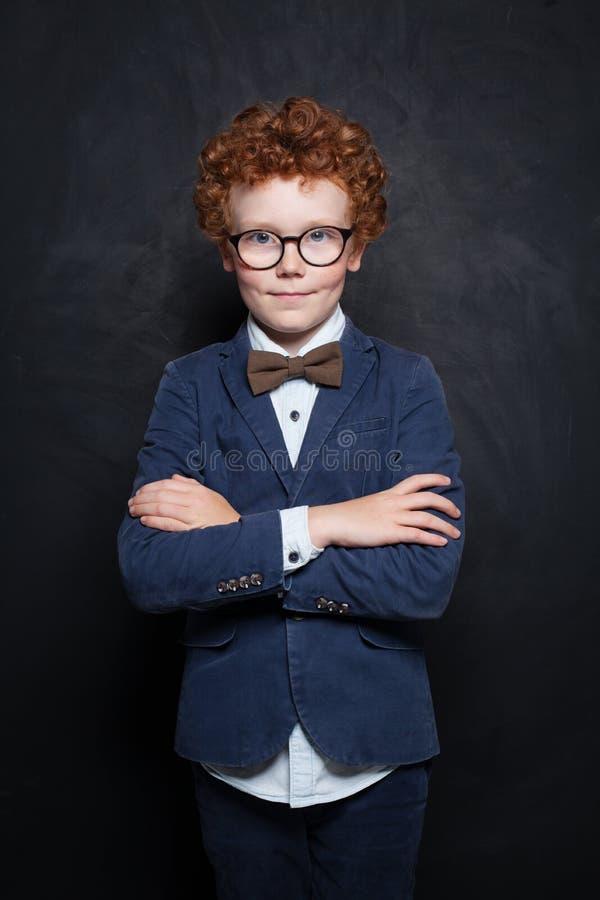 玻璃的聪明的儿童男孩在黑板背景的教室 聪明的学生画象 免版税库存图片