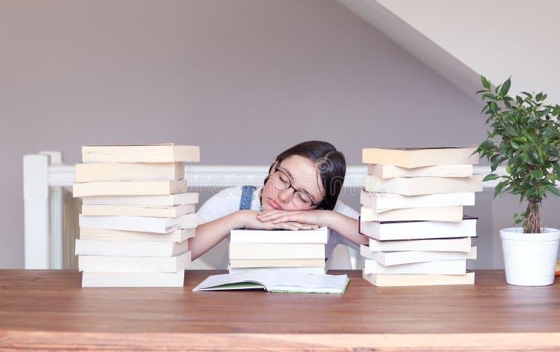 玻璃的逗人喜爱的滑稽的非离子活性剂女孩疲乏对读和学习平安睡觉与她的头在堆的书书之间 图库摄影