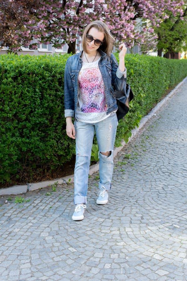 玻璃的青少年的女孩走在一个开花的佐仓公园的 步行在早期的春天 库存图片