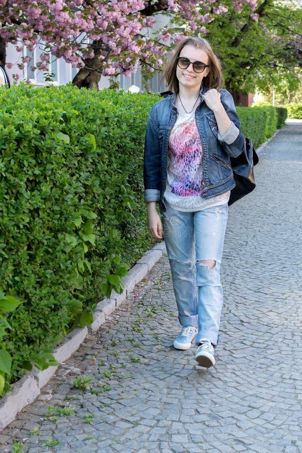 玻璃的青少年的女孩走在一个开花的佐仓公园的 步行在早期的春天 免版税库存图片