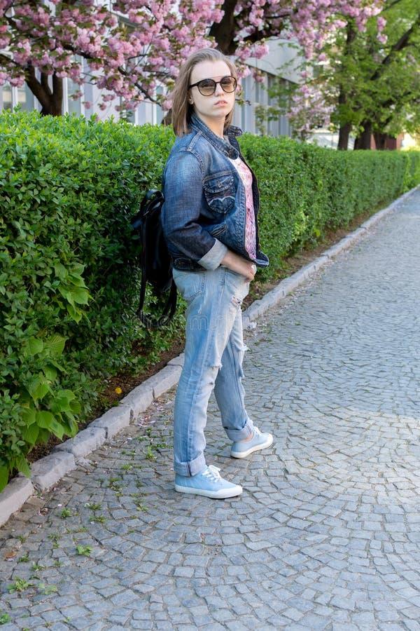 玻璃的青少年的女孩走在一个开花的佐仓公园的 步行在早期的春天 免版税图库摄影