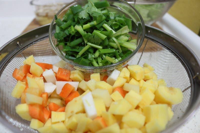 玻璃碗香菜、土豆、红萝卜和香葱切了 做一个健康盘的成份 库存图片