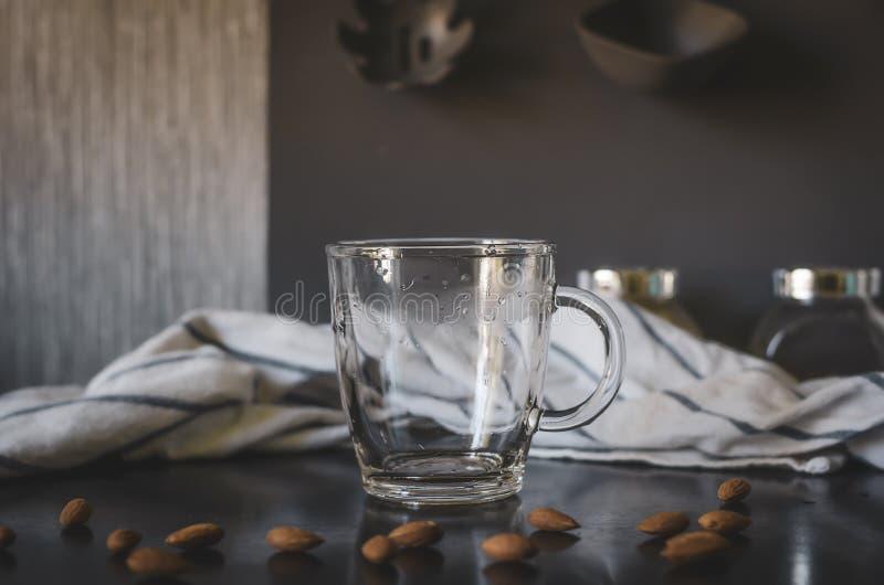 玻璃空的杯子 在杏仁附近,演出了照片 库存照片