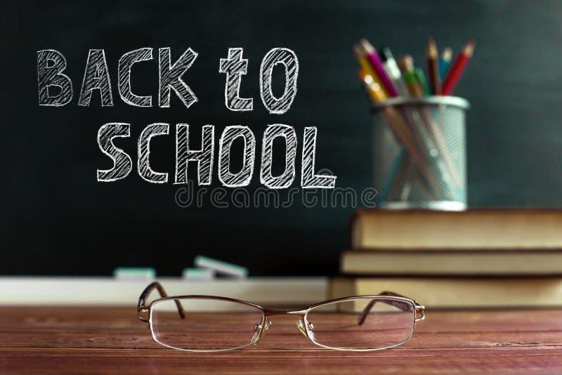 玻璃老师书和一个立场与铅笔在桌上,在一个黑板的背景有白垩的 概念的 库存照片