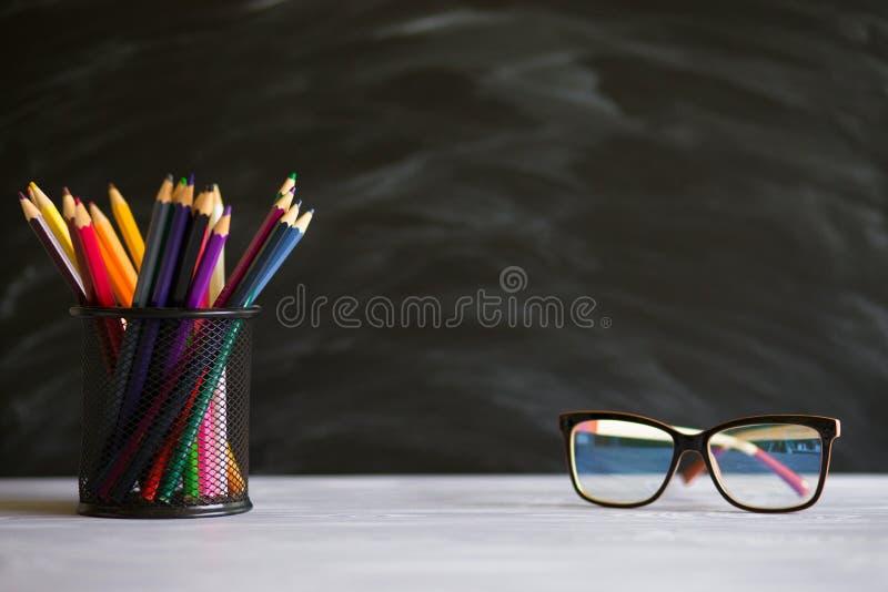 玻璃老师和立场与铅笔在桌上,在黑板背景有白垩的 老师的天的概念 免版税库存照片