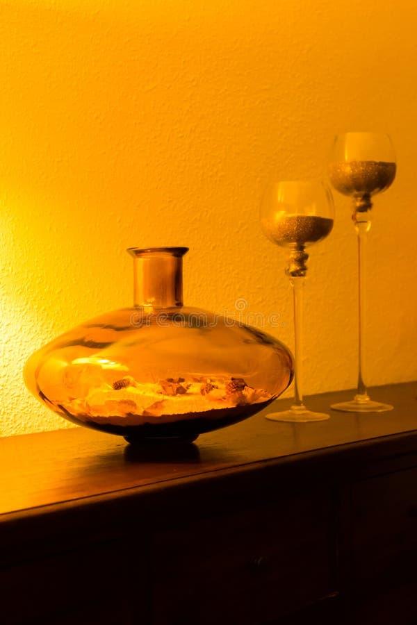 玻璃花瓶和烛台在洗脸台在夜橙色照明设备 室内设计元素 免版税库存图片