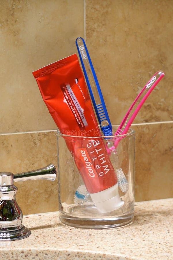 玻璃花瓶拿着牙膏和刷子在卫生间工作台面 图库摄影