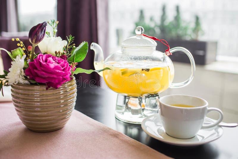 玻璃茶壶用与菠萝切片的热的菠萝茶在咖啡馆 一个杯子芬芳黄色茶、一个玻璃茶壶和美好的pi 免版税库存图片