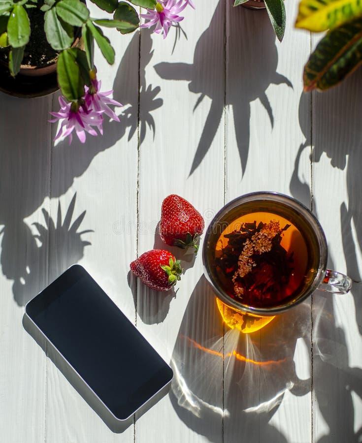 玻璃茶的特写镜头图象、红色草莓、智能手机和花在罐在轻的木背景 库存照片