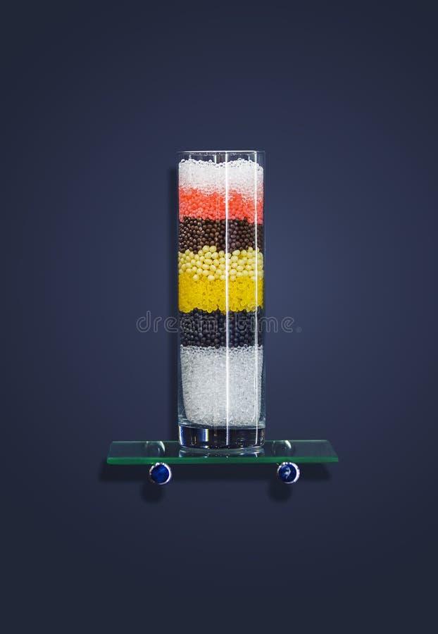玻璃装饰测试管小瓶、一个花瓶有色的沙子的和小珠在它 在一黑暗的backg隔绝的装饰室内装璜 图库摄影
