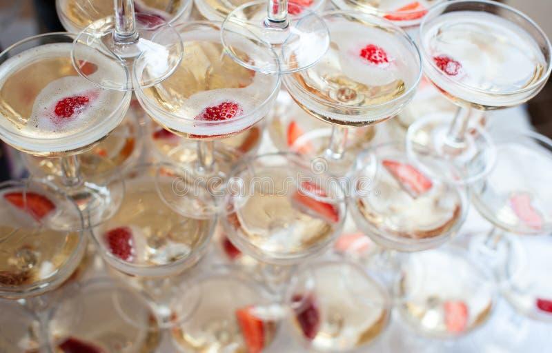 玻璃金字塔用香槟和草莓 免版税库存照片