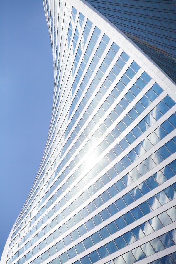 玻璃镜子摩天大楼墙壁在天空蔚蓝,白色云彩背景,现代商业中心大厦的螺旋形状 免版税库存图片