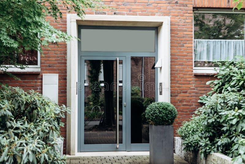 玻璃门的看法在入口的对住宅房子 免版税库存图片