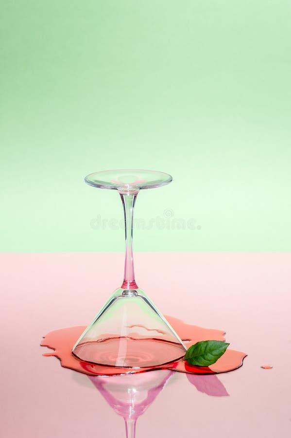 玻璃马蒂尼鸡尾酒玻璃和溢出的液体在桃红色绿的背景 现代艺术摄影 图库摄影