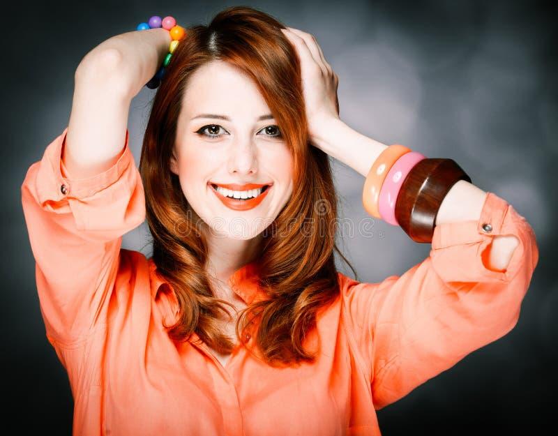 珊瑚衬衣的微笑的白种人红发成人女孩 免版税库存图片