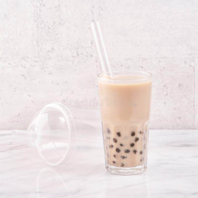 珍珠粉珍珠球泡影奶茶,普遍的台湾饮料,在与秸杆的水杯在大理石白色桌和木盘子上, 免版税库存照片