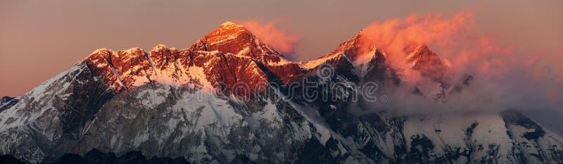珠穆朗玛峰洛子峰和努子峰南岩石面孔日落红色彩色视图与美丽的云彩的从Kongde村庄, 库存照片