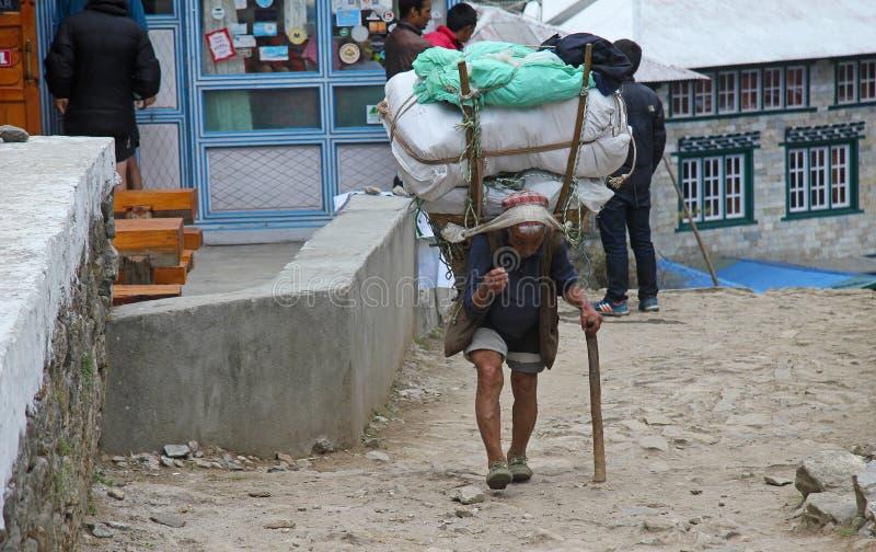 珠穆琅玛阵营,国家公园,尼泊尔- 4月15 2017年 运载重的大袋的老sherpa搬运工 免版税库存照片