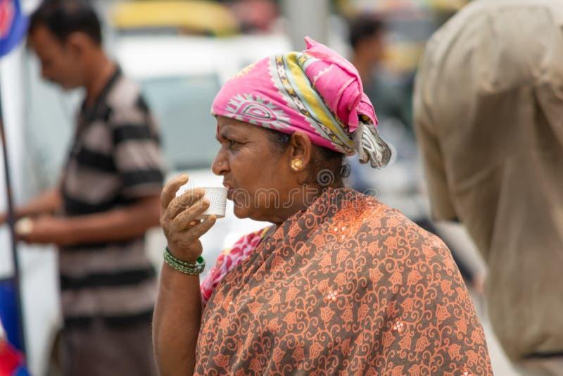 班加罗尔,卡纳塔克邦印度6月04日2019年:印度在街道上的妇女饮用的茶在完成工作以后 免版税库存照片