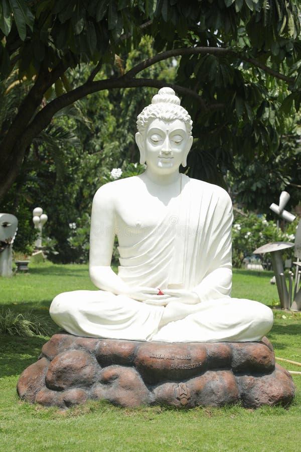 班加罗尔,卡纳塔克邦印度6月04日2019年:在思考的姿势的白色菩萨雕象在与自然的石桌上作为背景 免版税库存照片