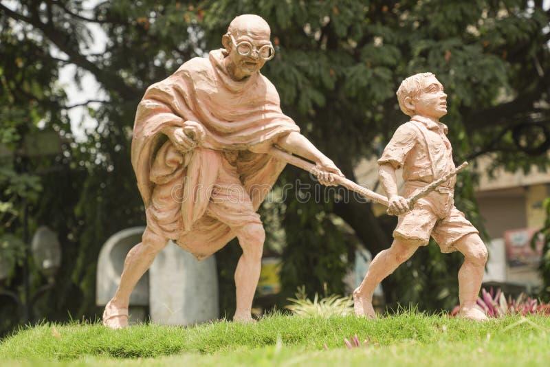 班加罗尔,印度,2019年6月4日:圣雄甘地和孩子,移动通过拿着的孩子雕塑圣雄甘地棍子  免版税库存照片