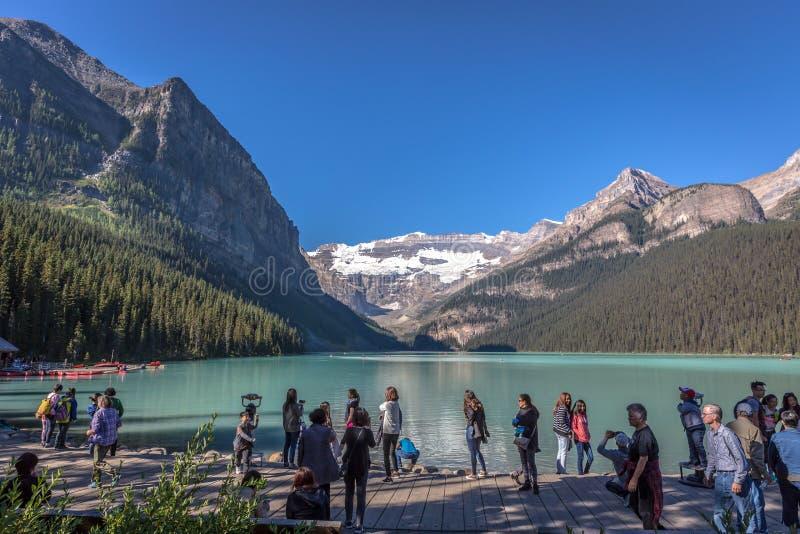 班夫,加拿大-前第14 2017年-小组在湖冰碛前面的游人在清早 蓝天,在backgr的山 库存照片