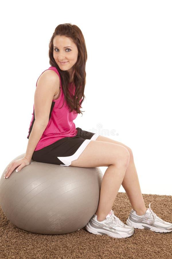 球健身桃红色坐的妇女 免版税库存图片