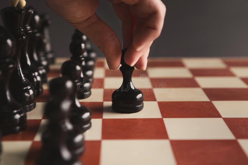 球员投入黑典当的棋盘比赛的手 免版税库存照片