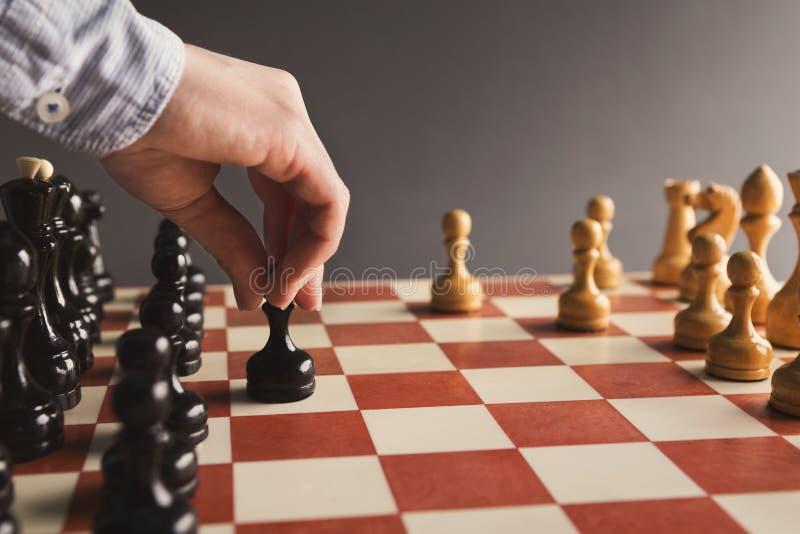球员投入黑典当的棋盘比赛的手 免版税库存图片