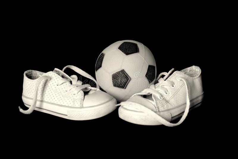 球和运动鞋在黑背景 免版税库存照片
