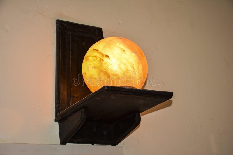 球在一个木架子托架的盐灯|喜马拉雅盐 免版税库存图片