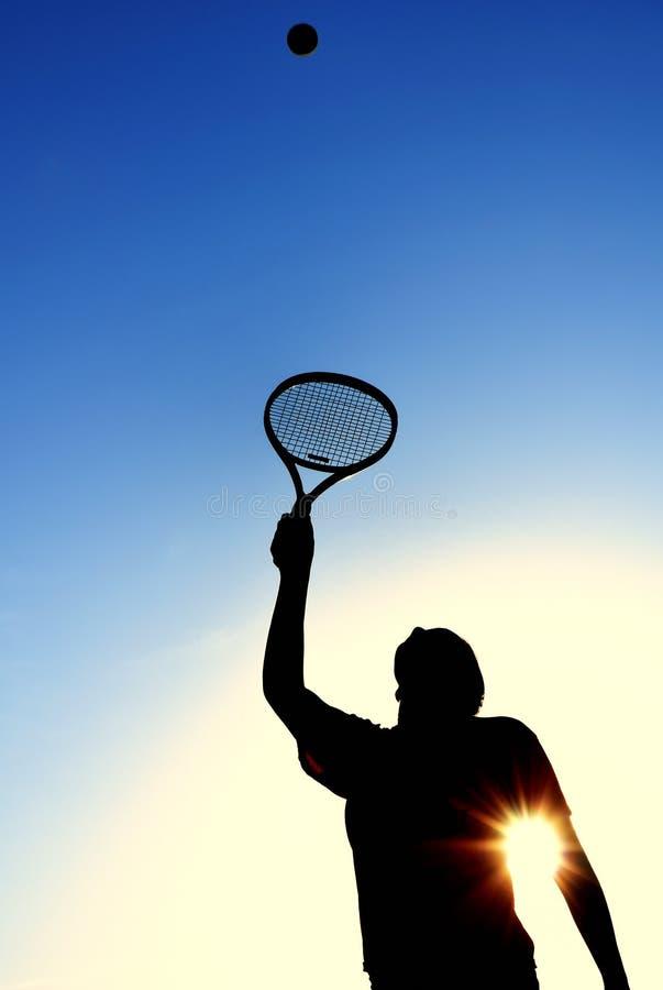 球女孩服务剪影青少年的网球 免版税库存照片