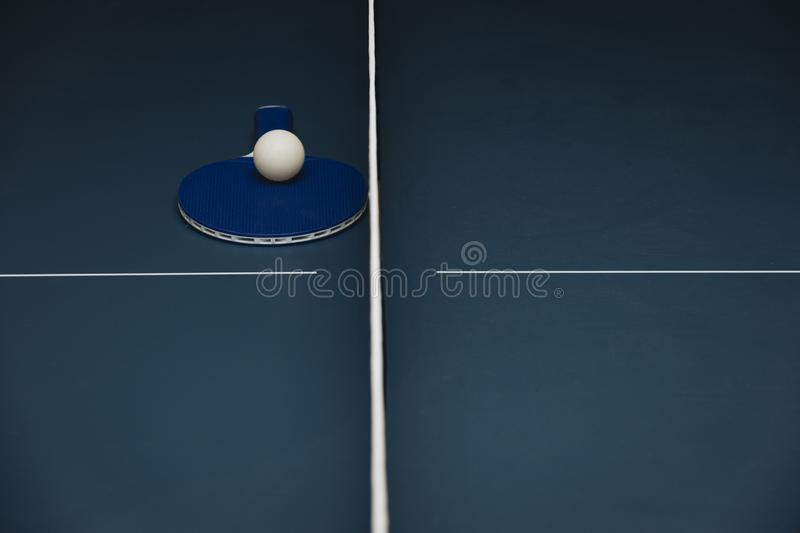 球拍、白色球和网在蓝色乒乓球网球桌上 免版税库存图片