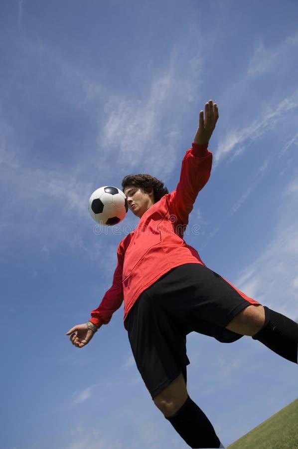 球控制足球运动员红色足球 库存图片