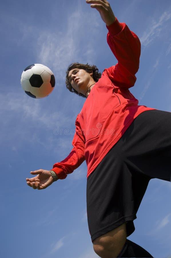 球控制足球运动员红色足球 免版税库存照片