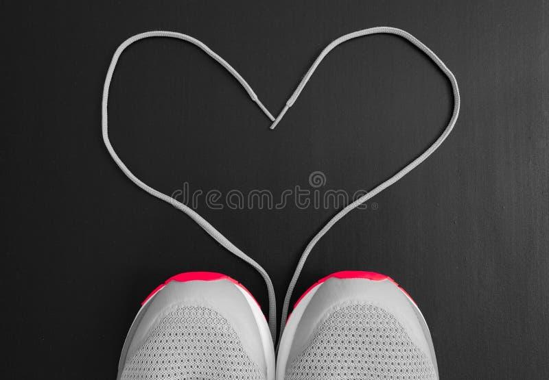 球概念健身pilates放松 对体育的爱 运动鞋炫耀有鞋带的鞋子作为心脏的形式在黑背景的 免版税库存照片