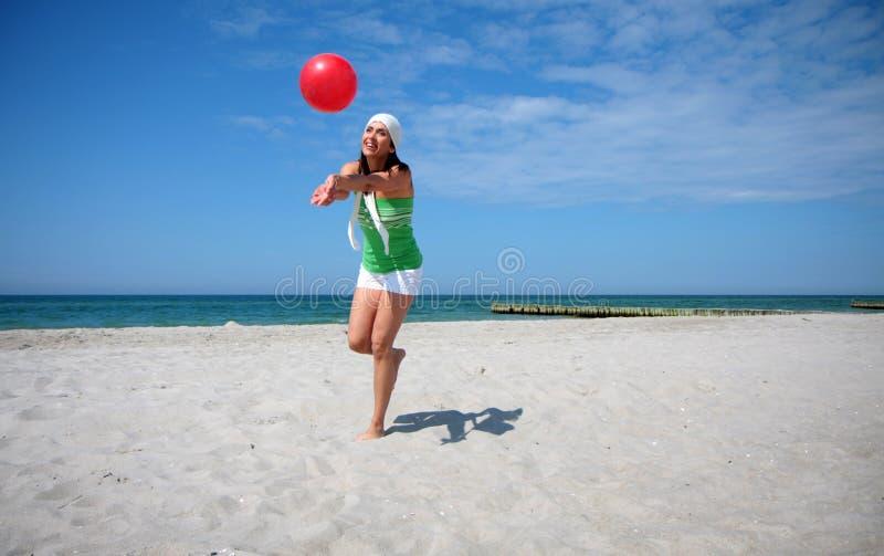 球海滩跳的妇女 免版税库存照片