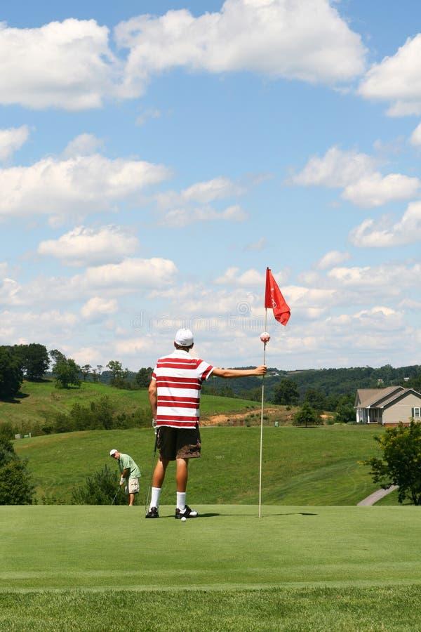 球父亲放置儿子趋向于的标志高尔夫&# 免版税库存照片