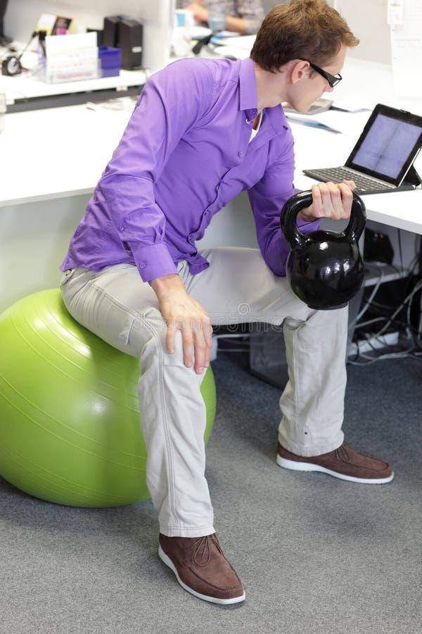 球的人解决与kettlebell的在offce工作期间 免版税库存照片
